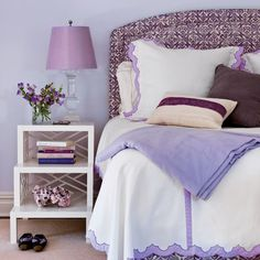 Soothing Hue. Pale lavender appears in the lampshade and sheet trim, while a deeper amethyst hue adds kick to the bed upholstery and accent pillows. The walls are painted Spring Iris by Benjamin Moore.