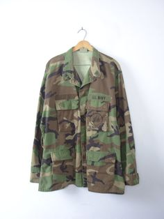 One vintage 1990s distressed grunge camo jacket, military camo shirt, army camouflage fatigues, size XL - long  - Pointed collar with eagle patches at the corners. - 5 army green plastic buttons going down the center front, hidden under a fabric flap. - 4 pockets on the front with flaps and button closures. - Reinforced fabric elbow patches. - 3 adjustable buttons on wrist cuffs. - Patch on front reads U.S. Navy, with embroidery of Seabees underneath. - Color scheme: dark brown, army green…