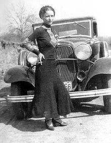 Bonnie Parker posere foran den sorte bil.