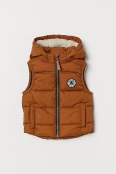 Padded vest with a lined, detachable hood, zip at front with chin guard, and welt side pockets. Lined. Treggings, Casual Outfits For Teens, Khaki Green, Printed Sweatshirts, Fashion Company, Kid Shoes, Black Print, World Of Fashion, Canada Goose Jackets