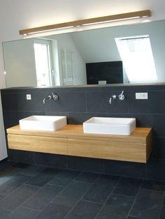 Eichebadmöbel schwarze Fliesen weiße Badkeramik