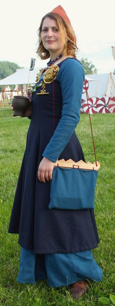 My Hedeby dress in woad dyed twill is finished. Handsewn with waxed linen thread. I love the way the double side panels ended up. Here seen together with a York cap in wool, an apron dress and my new bag based on the wooden Birka handles. The drinking vessel is also Birka.