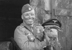 Soviet soldier putting SS hat on a pig