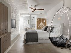 This boutique hotel room in Mykonos features decorative artistic wooden panels hanging from the ceiling.