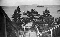 Looking out across the Bay at Geelong. A flight of steep wooden steps leads down to the beach. A sailing ship and several small watercraft are at anchor in the Bay. The You Yangs can be seen in the distance.