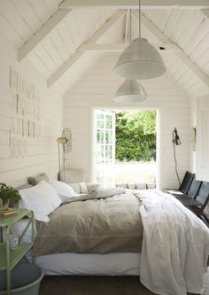 Dit hoge plafond is enorm geschikt voor de industriële hanglampen. Het hout en de openslaande deuren maken deze kamer sfeervol.