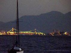 A Ponte Hercílio Luz iluminada por trás do veleiro na baía de Sto.Anto.Lisboa