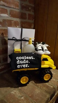 """Baby boy shower gift. Tonka truck filled with gift box with outfits, baby wash, butt paste, baby wipes, """"coolest dude ever onesie, and infant black high top converse tennis shoes"""