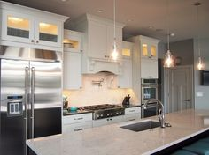 White kitchen with dark wood island and stainless steel appliances.