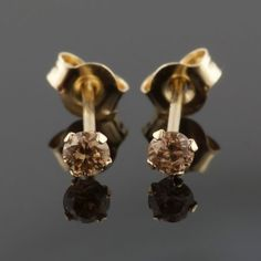 This is a beautiful pair of .25 carat, Natural Fancy Chocolate Champagne Brown, Round Brilliant shape and cut Gold Diamond Earrings with an VS clarity. A beautiful Natural Fancy Champagne Brown Color that look stunning in these diamond earrings. These chocolate brown diamond earring studs have an amazing color and are set in real solid gold.  Let one of our Diamond Specialists help you.