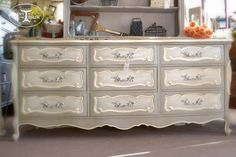 """This piece was painted by """"paint in my Hair"""" spokane, by hand using Chalk Paint decorative paint. French Linen on the body, French Linen & Old White Striae on the drawers, and Graphite underneath silver leafing on the handles. The entire piece was triple waxed–first Annie Sloan Clear Soft Wax to seal it, Dark Soft Wax to antique it, and another coat of Clear Soft Wax to finish it up!"""