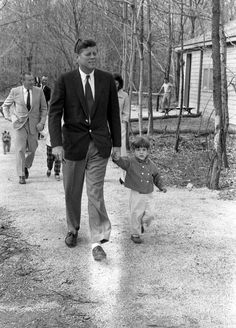 Taking a stroll: The president takes his son for a walk, while the first lady walks behind the pair as she chats with Under Secretary of the Navy Paul 'Red' Fay and his daughter, Sally
