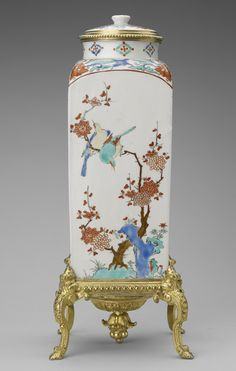 A pair of Japanese Kakiemon, square, porcelain vases with rounded shoulders and short cylindrical necks, and domed covers; decorated with birds and plants, each on an ormolu stand with cabriole legs, foliate feet and a central pinecone finial in the centre on a gadrooned base with a wreath rim.