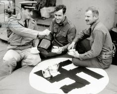 A U.S. Coast Guard is serving tea for two infantry officers. 1944. A Nazi flag with a Swatika is serving as tablecloth. The Channel., 1944