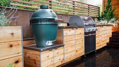 Cedar cabinetry and stainless steel countertops give this outdoor kitchen a modern feel; herb gardens filled with lavender, yucca, and juniper give the space a natural feel.  See more of this outdoor kitchen at New Eco Landscape Design & Build.