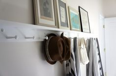 "Shaker peg rails (6"" apart) from Peg and Rail, which offers a shelf and various finish options. the shelf allows you to display art without having to commit to hanging it. Photograph by Christine Chang Hanway. White Shaker Peg Rail with shelf in hallway, straw hats and towels, framed artwork 