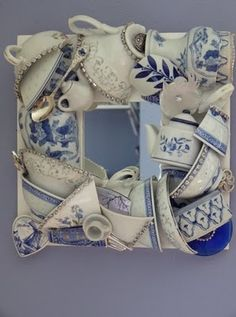 a framed mirror made with tea cups