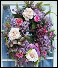 Beautiful purple,pink and cream roses with a bunch of hanging grapes and small bird.
