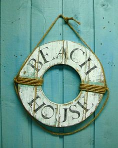 I wanna DIY this thing.    Beach House Sign Life Preserver Ring Wall Hanging Nautical Decor. $79.00, via Etsy.