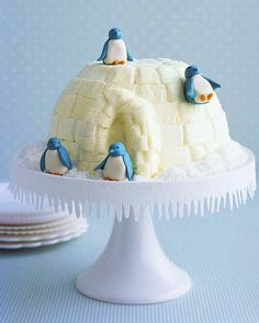 """Piped buttercream-frosting blocks transform a chocolate-vanilla ice cream cake into an igloo that sweet marzipan penguins call home. Flakes of dried coconut """"snow"""" and a cake stand trimmed with sugar-dusted paper icicles complete the icy habitat (download the icicle template)."""