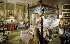 For a snuff-color master bedroom in the Philippine capital of Manila, Buatta lined the theatrical bed's carved-wood canopy with a shaped valance made from a flame stitch–pattern fabric by Old World Weavers. The same fabric shows up on a low chair, while textiles from Brunschwig & Fils upholster the settee and club chair.