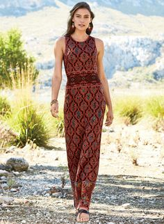 Long and lithe, the shoulder-baring maxi-dress enchants, knit in rich motifs from an Indonesian textile. In sun-warmed shades of Sedona red, teal, amber and black, it's styled with a high neck, contoured tank straps and gorgeous contrast banding at the waist and hem.
