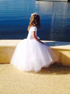 A romantic length tutu created in white tulle with a white satin luxury ribbon sewn to worn at the natural waist. Light as feather and so very dainty-- just like a little girl. It is sure to thrill your wedding party. And after the wedding? It also makes the most elegant portrait tutu. You may change the ribbon color if you prefer. If you need this skirt longer than 26, please order the extra long tutu skirt for girls…