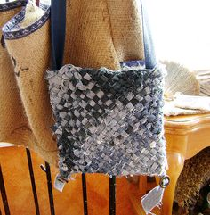 bag from woven denim strips/ made pn a triangle loom. 2 triangles made into a square for each side. sewn together and then sewn around to make a bad shap.  handles from long strips of denim clean not ragged like the bag.  i would put a lining and a pocket.
