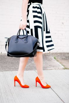Black-white striped skirt, black T-shirt, red heels, black Givenchy Antigona bag