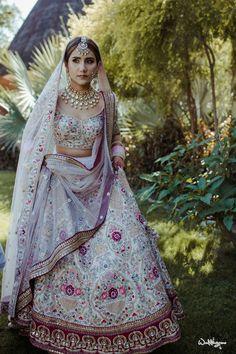 Bride in a white lehenga with embroidery on the lehenga skirt and blouse with an elegant necklace and a maangtikka #bride #bridalwear #bridallehenga #lehenga #indianwedding #weddingoutfit #white #embroidery #necklace #maangtikka #jewelry #bridaljewelry #shaadisaga