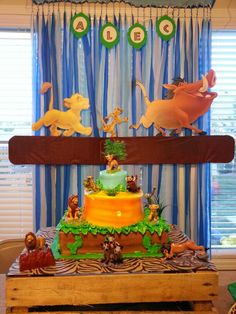 Lion King themed birthday party. Cake ideas. Customized cake from Publix. I bought the cake toppers on Amazon. Wrapped the top part of a crate with animal print wrapping paper from Dollar Tree. Hakuna Matata backdrop