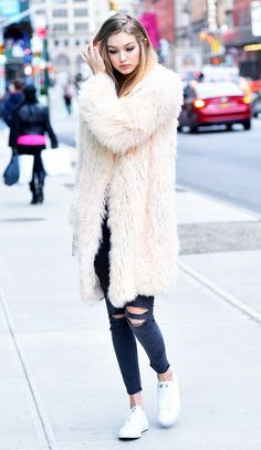 Gigi Hadid wears a statement fur coat over her casual outfit.