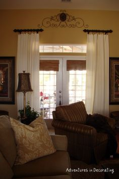 Window Treatments for French Doors - short rods are placed well above and to the outside of the door frame. This makes the door appear wider and it draws the eye up. This would be a perfect way to add privacy to your front door's sidelights - via Adventures in Decorating