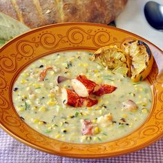 Lobster and Grilled Corn Chowder - a lighter version of a New England style chowder using no cream and 1% partly skimmed milk. Succulent lobster, grilled sweet corn and fresh herbs are central to the success of this delicious chowder. The quickly grilled lemon wedges get served with the chowder to be squeezed in before eating for a final layer of flavor and burst of freshness.
