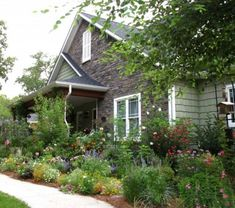 create a cottage feel in a large garden bed, and let the plants billow over onto the sidewalk to soften the space.