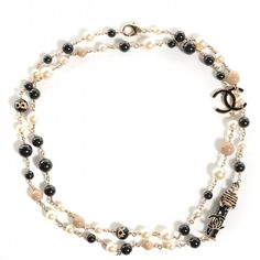 This is an authentic CHANEL Pearl CC 100th Anniversary Coco Charm Necklace in Black,  Beige, and Gold. This versatile necklace may be worn doubled or as one long strand.