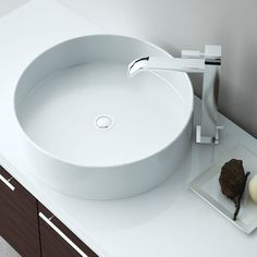 Circular Basin by Blu Bathworks on a white vanity tower with tall sleek rectangular mirror over top