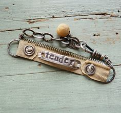 """nice idea for a bracelet - Think denim would look great! recycled vintage zipper, sewn to two sterling hammered circles and attached with a couple of my cast sterling buttons from my studio collection; sewn to the center is one of my PMC (precious metal clay) silver ID pieces into which i've hand stamped the word """"tender""""; a silverplace watch fob clasp and a sterling bit of heavy chain allow for adjustment in size. Dangling from the end carved round mother of pearl antique button"""