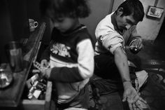 A young girl, left, searches for something in a cupboard drawer, while her father's friend, Pakori, injects drugs.