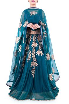 This emerald green lehenga is designed on lotus motif. It features lotus embellishment all over the body designed shimmer appliqué and gota lace and featuring contrasting navy blue lining. The lehenga is paired with a broad v neck sleeveless wine blouse decked with gota lace work and completed with a net dupatta again in emerald and designed with lotus motifs and a delicate border.