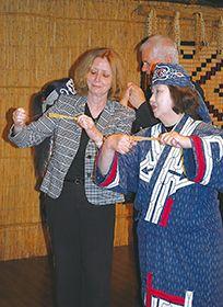 ムックリの演奏に挑戦するカハノフ大使(左)