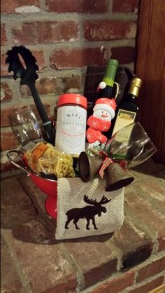 Italian pasta, sauce, seasonings, bread sticks, wine, and wine,glasses. Christmas themed gift basket in a festive red collander.