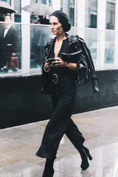 Erin Wasson wears a black belted jumpsuit, draped leather jacket, black platform boots, a single earring, and a black beret