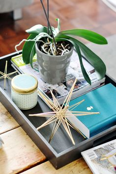 Trays are a great addition not only to carry your coffee to your table, but to group small items together. It's a visual trick: grouping lots of small items on a tray will make your table look tidier and give the impression of a well thought out collection rather than a random amassment of items all lying around the table. Just one tray with items layered on top of each other is enough for any coffee table.