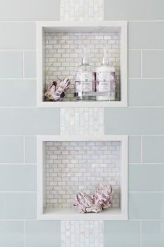 Blue subway shower tiles frame two white glass mini brick tiled shower niches connected by white glass iridescent accent tiles.