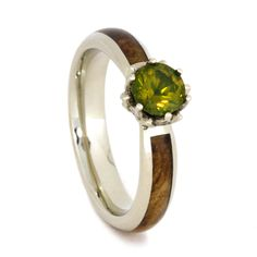 This peridot engagement ring is crafted in white gold, with a natural black ash burl inlay. The incredible lotus setting is decorated with sparkling...