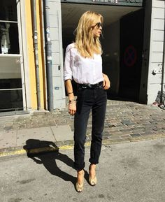 Pernille Teisbaek wears a white button-down shirt, belted black cuffed jeans, and snakeskin peep-toe heels