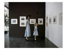 Mrs. John Heminway and her daughter Hilary admire the art hanging in the Museum of Modern Art in New York City, 'Vogue' magazine, April 1948. Mrs. Heminway wears a blue cotton chambray dress by Mildred Orick and a wide-brim hat by Dobbs; Hilary's similar frock is by Ellen Hewitt.  Photo by John Rawlings.