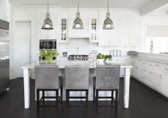 """The kitchen is designed for functionality with a 48"""" Subzero refrigerator and Wolf range. Add in the marble countertops and industrial pendants over the large island and you have a stunning area.  (Cultivate.com)"""