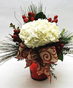 Overflowing with holiday greens, a big gorgeous white hydrangea, and dotted with stems of red hypericum berries, this arrangement is the perfect touch for an office desk, or as decor for the home!